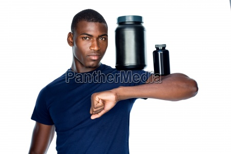 fit man holding bottles with supplements