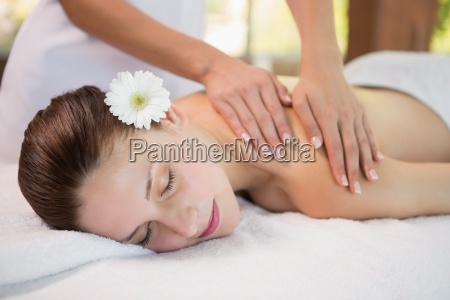attractive woman receiving shoulder massage at