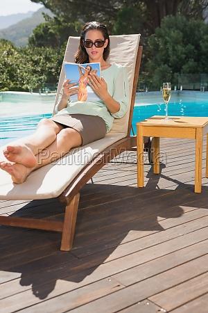 woman reading book on sun lounger