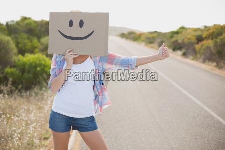 woman with smiley face hitchhiking on