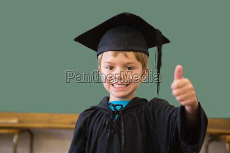 cute pupil in graduation robe smiling