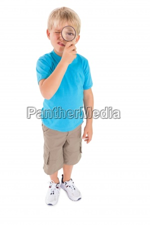 cute little boy looking through magnifying