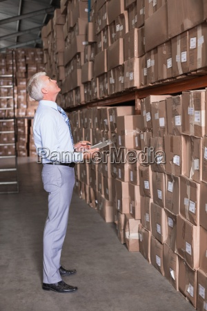 warehouse manager checking his inventory