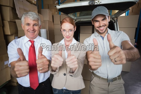 warehouse managers and delivery driver smiling