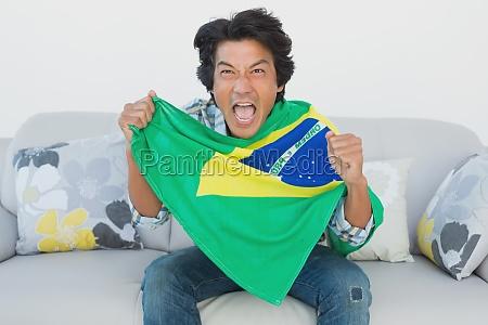 brazilian football fan cheering while watching