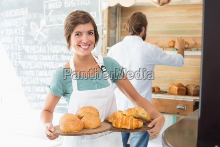 pretty barista holding trays of baked