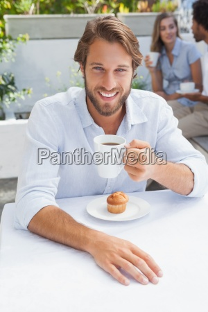 happy man having coffee and muffin