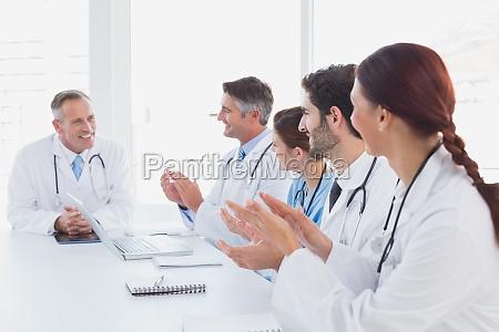 doctors applauding a fellow doctor