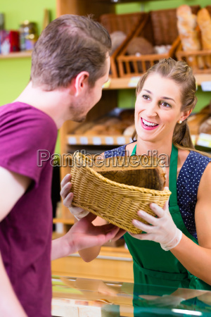 bakery saleswoman offers customers bread