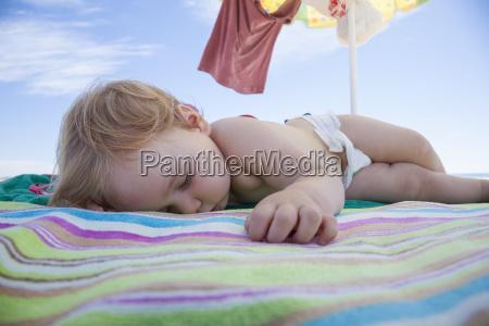baby sleeping on beach towel
