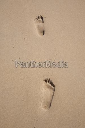 both feet footprints on sand beach