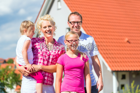 family stands proudly in front house
