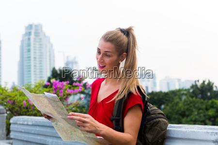tourist sightseeing with city map in
