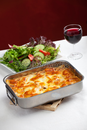 baking dish with lasagna and salad