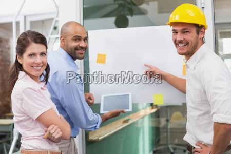 smiling architect team brainstorming together using
