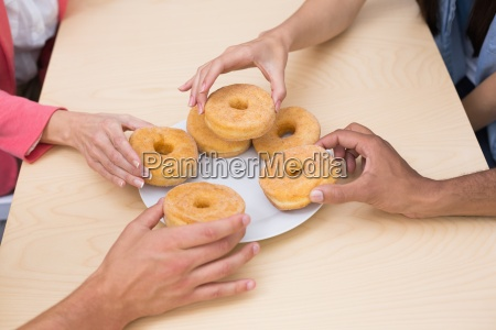 business team reaching for doughnuts on