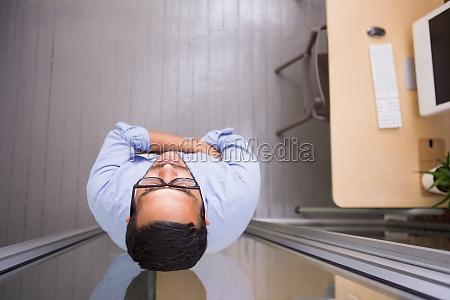 tankevaekkende forretningsmand staende mod glasvaeg pa