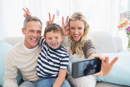 cheerful family taking self pictures with