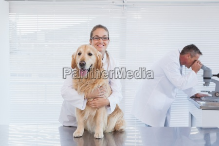 smiling doctor holding a labrador