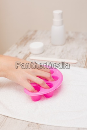 woman soaking her nails in nail