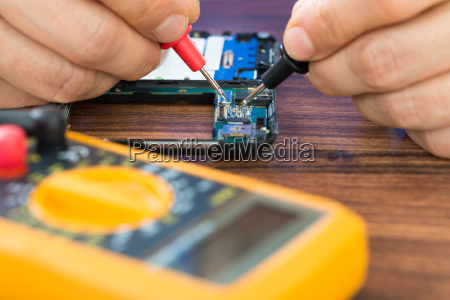 human hand repairing cellphone with