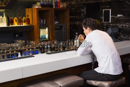 young man drinking whiskey neat