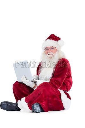 santa sits and uses a laptop