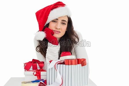 unsure brunette in santa hat packing