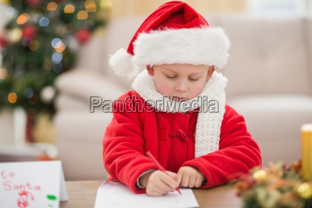festive little boy writing wish list
