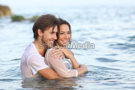 feliz pareja enamorada abrazando y banyandose