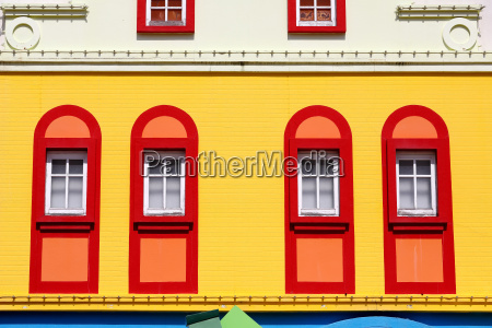 closed red window on colorful yellow