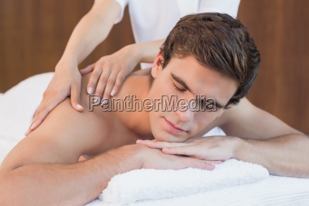 young man receiving shoulder massage at