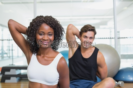 fit couple warming up on exercise