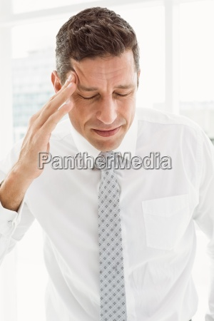 young businessman with severe headache in