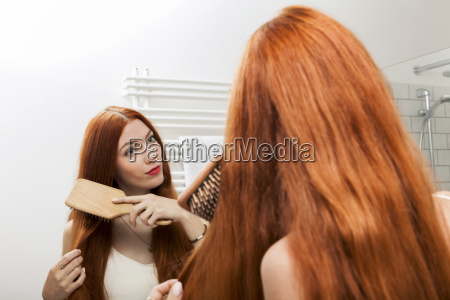 young woman with red hair brushing