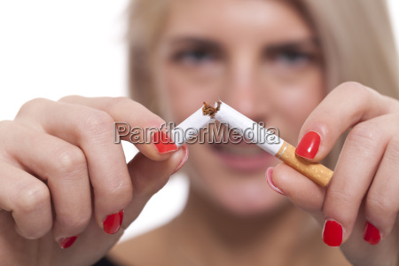 young blonde woman breaks a cigarette