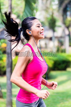 asian woman running in park for