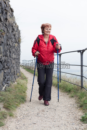 senior woman nordic walking on rocky