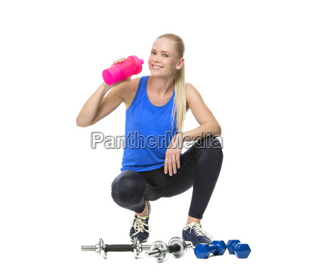 woman in fitness clothing drinking