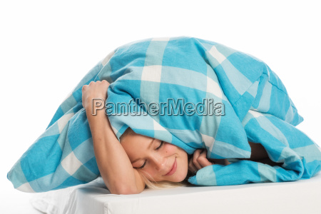 woman snuggles under the covers and