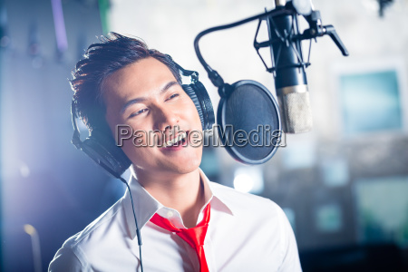 asian male singer producing song in