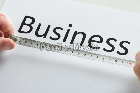 person hand measuring the text business