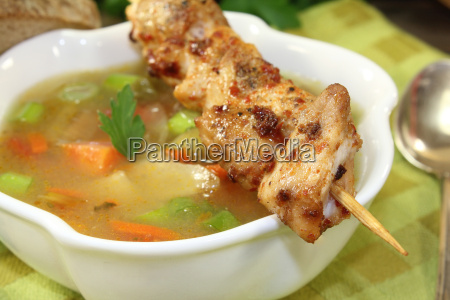 gefluegelconsomme with chicken skewers and soup