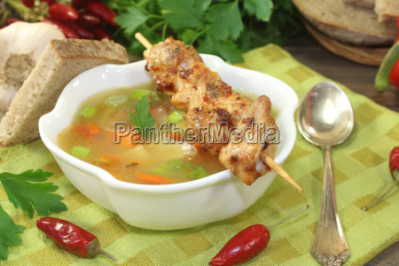 gefluegelconsomme with chicken skewers and parsley