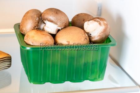 mushrooms in refrigerator with open door