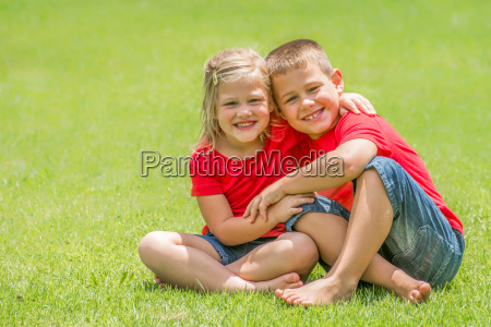 brother and sister on lawn hugging