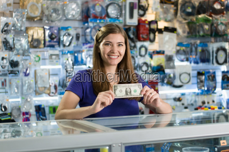 happy female computer shop owner showing