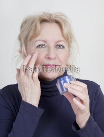 elderly woman with wrinkle cream