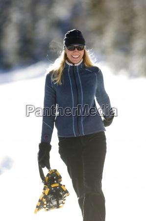 mujer con raquetas de nieve en