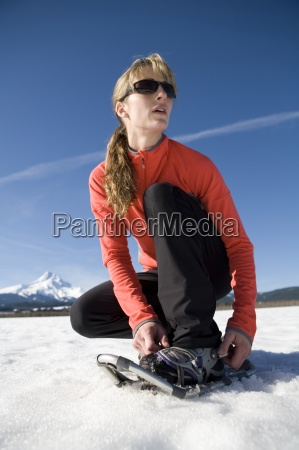 young woman straps on snowshoes with